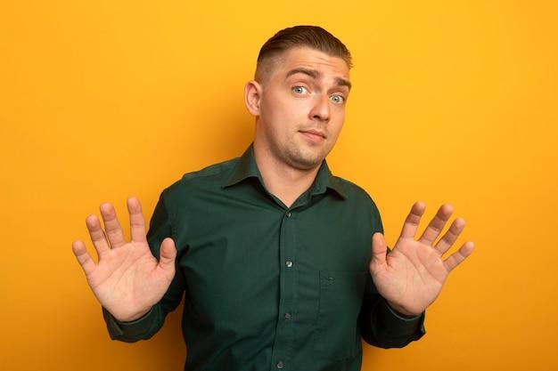 Junger hübscher mann im grünen hemd verwirrte das heben der arme in der übergabe