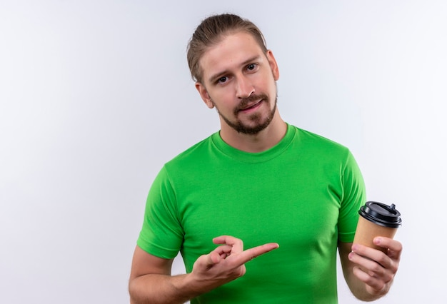 Junger hübscher mann im grünen t-shirt, der tasse kaffee hält, der mit dem finger auf ihn schaut, der zuversichtlich steht, über weißem hintergrund zu stehen