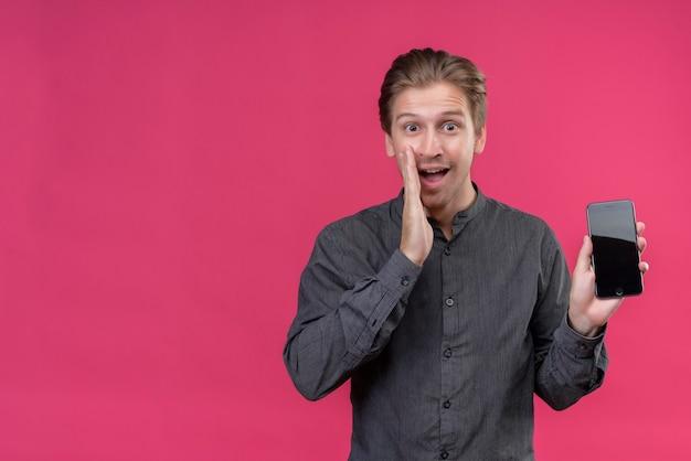 Junger hübscher mann im schwarzen hemd, das smarthone zeigt