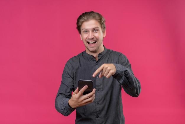 Junger hübscher mann im schwarzen hemd, der handy hält, das mit finger auf es zeigt