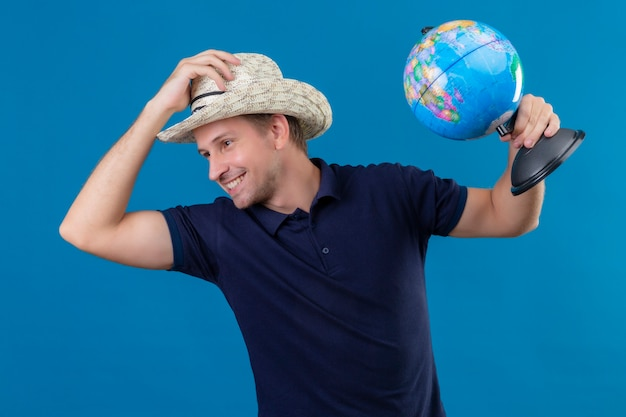 Junger hübscher mann im sommerhut, der globus hält, der seinen hut berührt, der mit dem selbstbewussten lächeln auf gesicht steht, das über blauem hintergrund steht