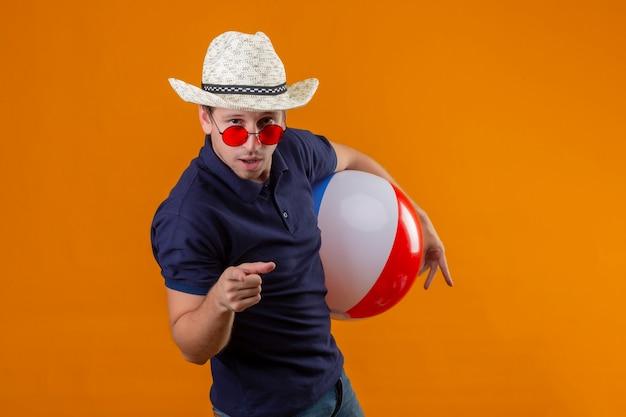 Junger hübscher mann im sommerhut, der rote sonnenbrille hält, die aufblasbaren ball zeigt, der mit dem finger zur kamera mit dem sicheren blick zeigt, der über orange hintergrund steht