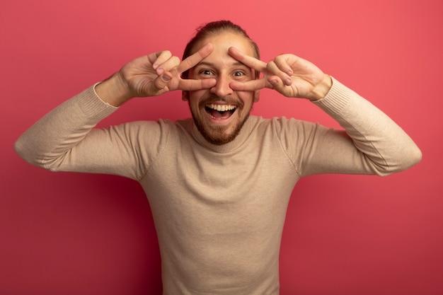 Junger hübscher mann in beigem rollkragenpullover, der vorne lächelnd fröhlich zeigt v-zeichen steht über rosa wand