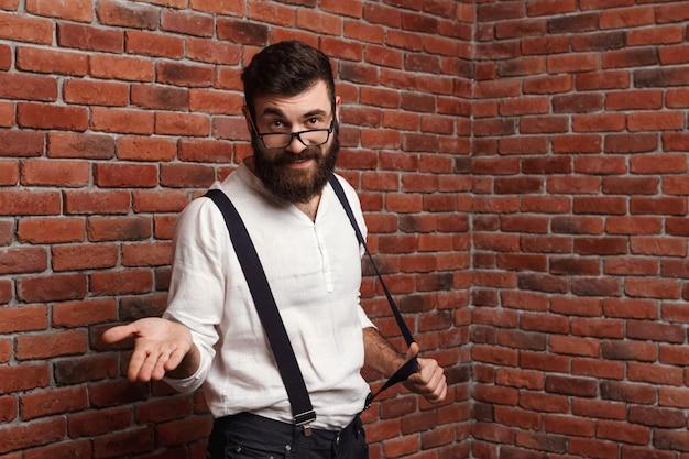 Junger hübscher mann in den gläsern, die auf ziegelmauer gestikulieren.