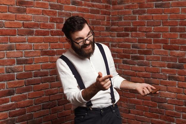 Junger hübscher mann in den gläsern, die auf ziegelmauer lachen.