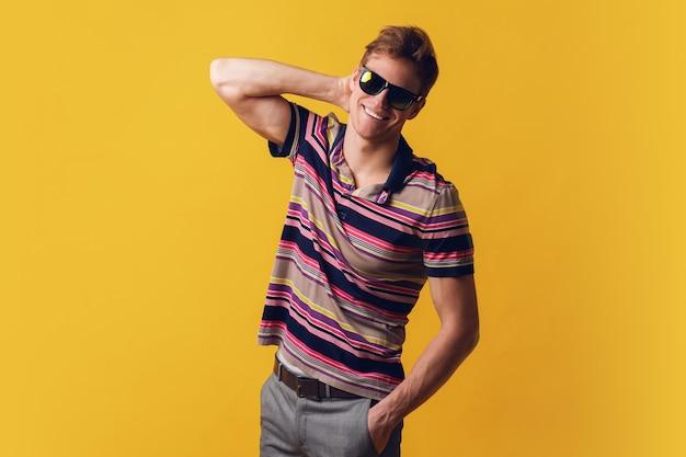 Junger hübscher mann in der sonnenbrille, die lässiges t-shirt trägt, das über gelbe wand steht, die mit lächeln auf gesicht, natürlicher ausdruck schaut. selbstbewusst lachen.