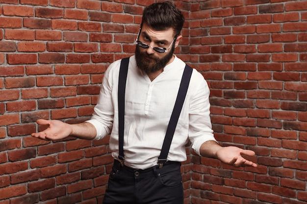 Junger hübscher mann in der sonnenbrille gestikulierend, die auf ziegelmauer aufwirft.