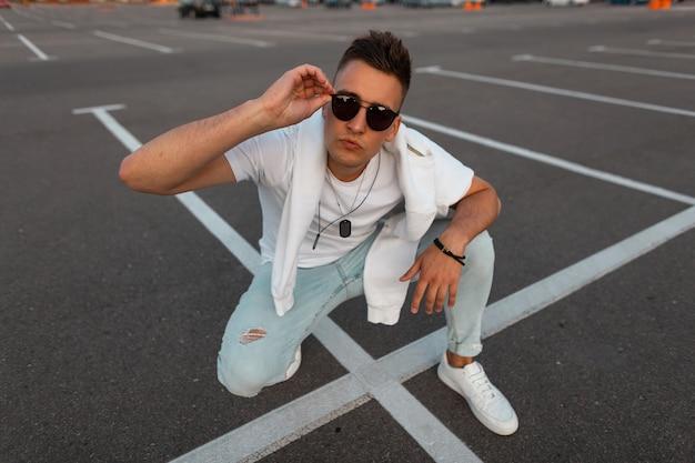 Junger hübscher mann in der sonnenbrille in den modischen blauen jeans in einem stilvollen weißen t-shirt in den turnschuhen sitzt auf der straße in der stadt an einem sommertag. kerl ruht auf der straße. sommer straßenmode