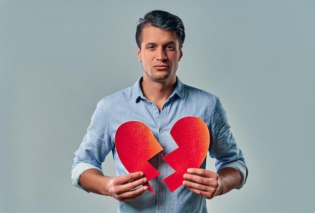 Junger hübscher mann in einem hemd hält ein gebrochenes herz in seinen händen auf einem grau.