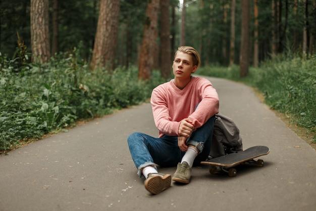 Junger hübscher mann in einem rosa modischen pullover mit einem skateboard sitzt auf asphalt im park