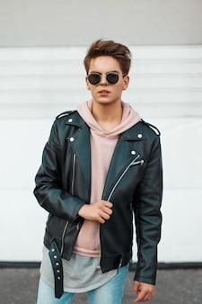 Junger hübscher mann in einer schwarzen markenlederjacke und einem rosa sweatshirt nahe einer weißen metallwand