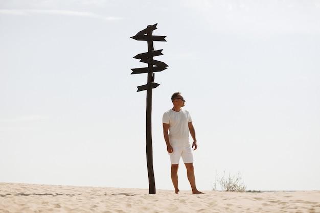 Junger hübscher mann in leichter kleidung und sonnenbrille nahe in der wüste