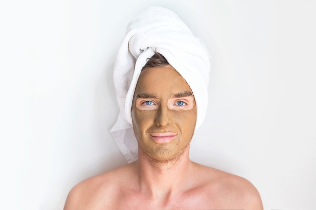 Junger hübscher mann, kerl mit kosmetischer tonmaske auf seinem gesicht und einem handtuch auf seinem kopf, lächelnd. beauty, spa, hautpflegekonzept. männer, die sich um die haut kümmern.