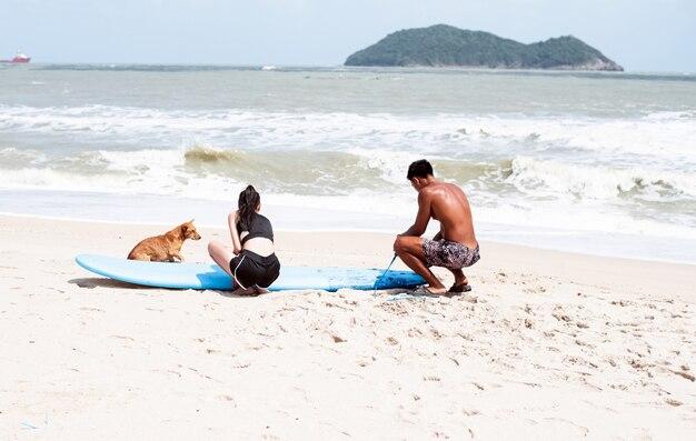 Junger hübscher mann kniet neben longboard nieder und zeigt, wie man seil um bein bindet