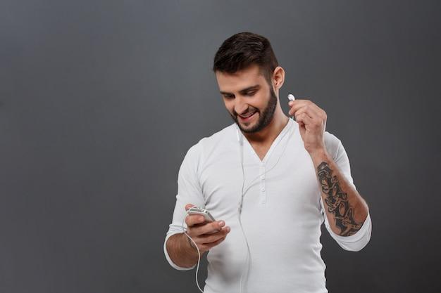 Junger hübscher mann lächelnd, der telefon über graue wand betrachtet