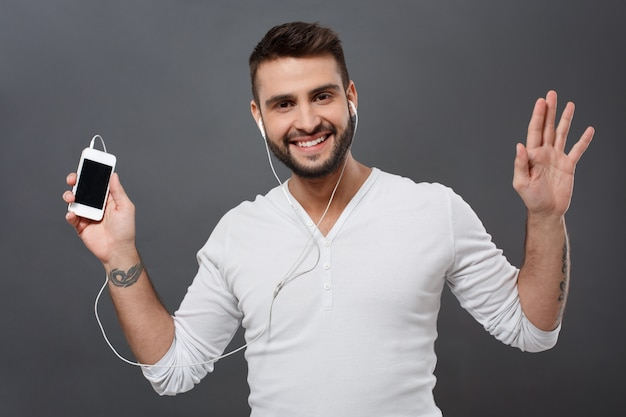 Junger hübscher mann lächelnd, der telefon über graue wand hält