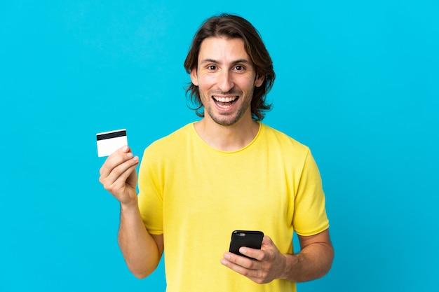 Junger hübscher mann lokalisiert auf blauem kauf mit dem handy und hält eine kreditkarte mit überraschtem ausdruck