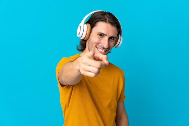 Junger hübscher mann lokalisiert auf blauer wand, die musik hört und nach vorne zeigt