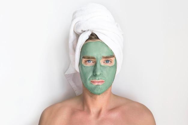 Junger hübscher mann, metrosexueller kerl mit kosmetischer lehmblauer maske auf seinem gesicht und einem handtuch auf kopf, lächelnd. beauty, spa, hautpflegekonzept. männer, die sich um die haut kümmern
