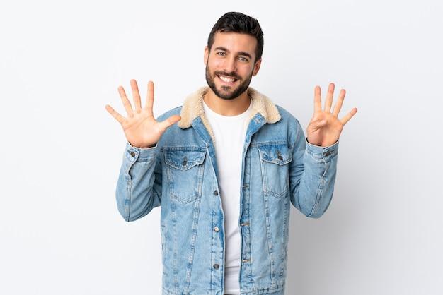 Junger hübscher mann mit bart lokalisiert auf weißer wand, die neun mit den fingern zählt