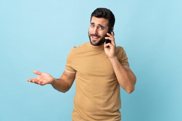 Junger hübscher mann mit bart über isolierter wand, die ein gespräch mit dem mobiltelefon mit jemandem hält