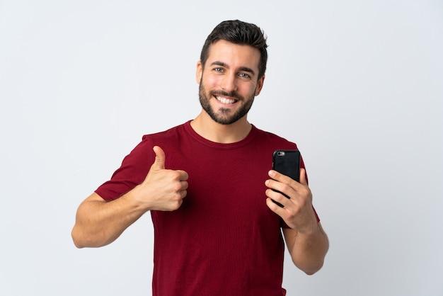 Junger hübscher mann mit bart unter verwendung des mobiltelefons lokalisiert auf weißer wand mit daumen hoch, weil etwas gutes passiert ist