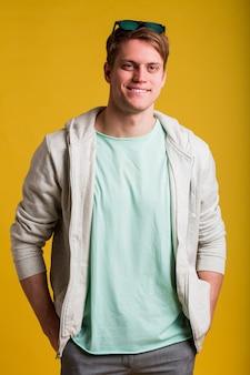 Junger hübscher mann mit dem tragen des lässigen t-shirts, das über gelbe wand steht, die mit lächeln auf gesicht, natürlicher ausdruck schaut. selbstbewusst lachen.