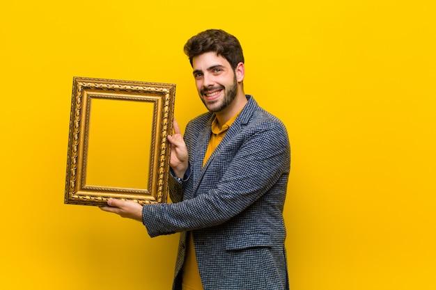 Junger hübscher mann mit einem barockrahmen gegen orange hintergrund