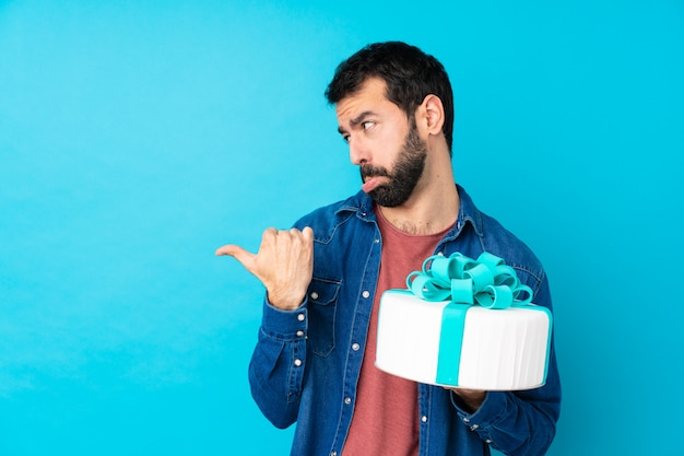 Junger hübscher mann mit einem großen kuchen über blau unglücklich und zur seite zeigend