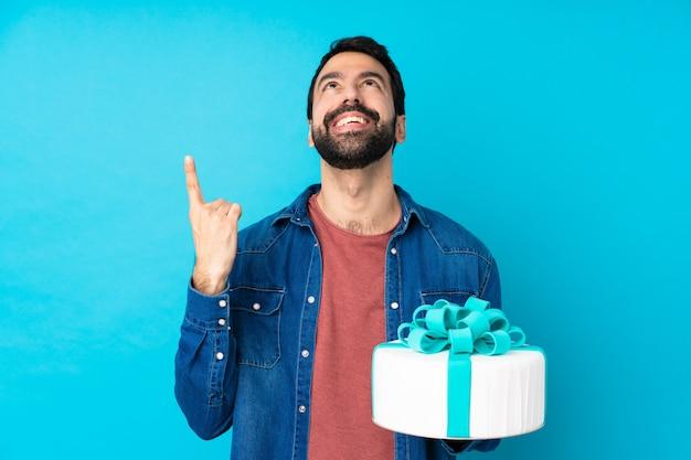Junger hübscher mann mit einem großen kuchen über der isolierten blauen wand, die oben zeigt und überrascht