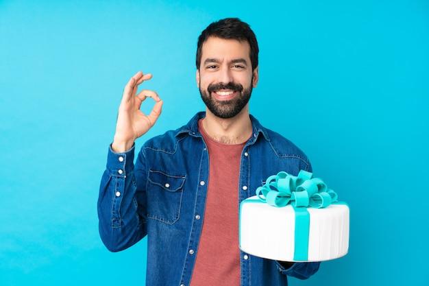 Junger hübscher mann mit einem großen kuchen über isolierter blauer wand, die ein ok-zeichen mit den fingern zeigt