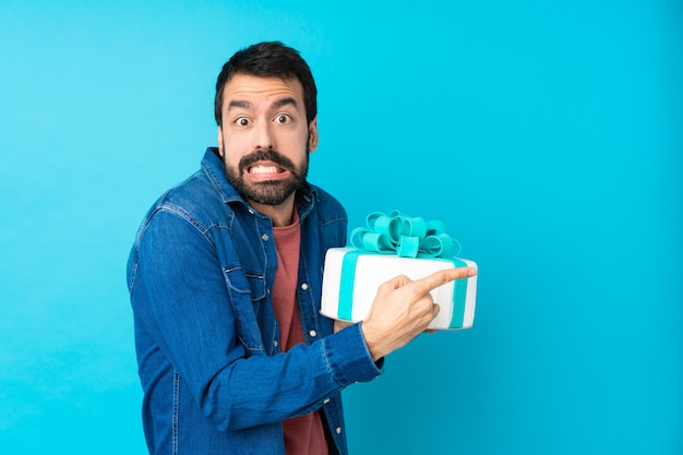 Junger hübscher mann mit einem großen kuchen über isolierter blauer wand erschrocken und zur seite zeigend