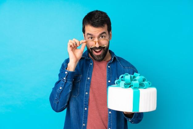 Junger hübscher mann mit einem großen kuchen über isolierter blauer wand mit gläsern und überrascht