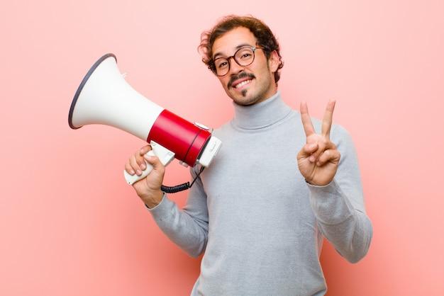 Junger hübscher mann mit einem megaphon gegen rosa flache wand