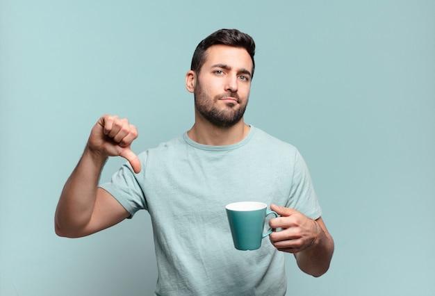 Junger hübscher mann mit einer kaffeetasse