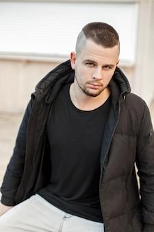 Junger hübscher mann mit einer kurzen frisur in einer stilvollen schwarzen winterjacke auf der straße