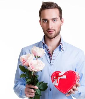 Junger hübscher mann mit einer rosa rosen und einem geschenk - lokalisiert auf weiß