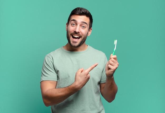 Junger hübscher mann mit einer zahnbürste.