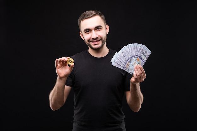 Junger hübscher mann mit goldenem bitcoin und mit dollargeld in der anderen hand lokalisiert auf schwarz
