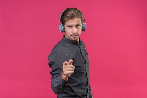 Junger hübscher mann mit kopfhörern, die mit finger nach vorne zeigen