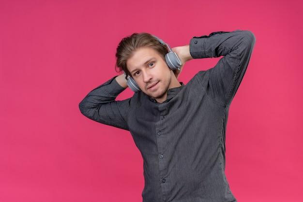 Junger hübscher mann mit kopfhörern, die seine lieblingsmusik genießen