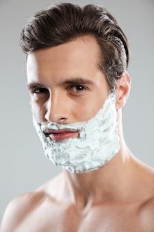 Junger hübscher mann mit rasierschaum auf gesicht
