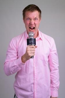 Junger hübscher mann mit rosa hemd und mikrofon