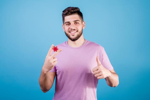 Junger hübscher mann mit rotem pokerchip auf blau