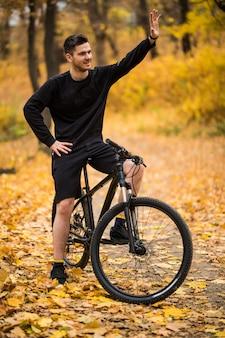 Junger hübscher mann mit seinem fahrrad, das hallo im herbstpark winkt