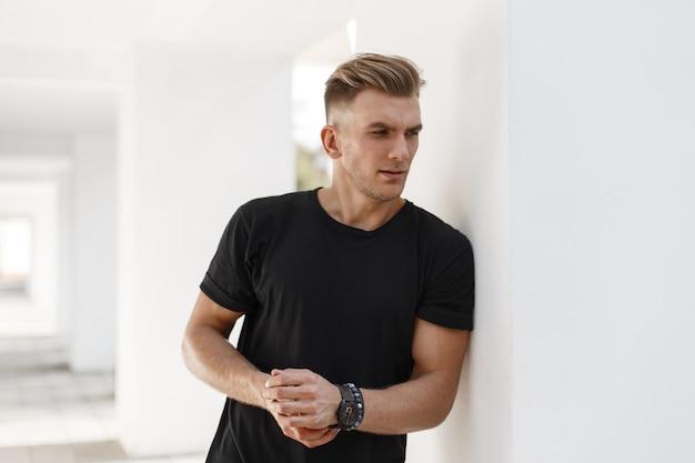 Junger hübscher mann mit stilvoller frisur im schwarzen t-shirt auf der straße