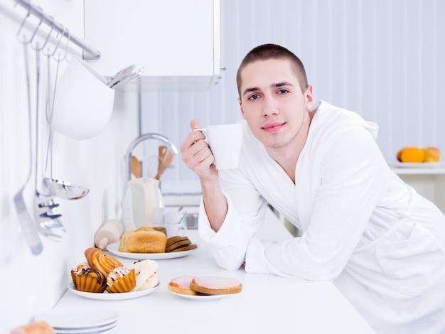 Junger hübscher mann mit tasse, die frühstück in der küche hat