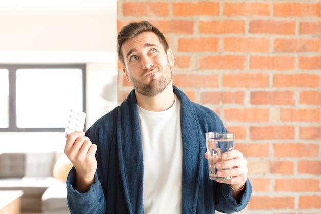 Junger hübscher mann mit wasser und pillen