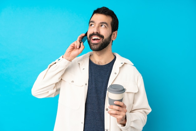 Junger hübscher mann mit weißer cordjacke, die kaffee zum mitnehmen und ein handy hält