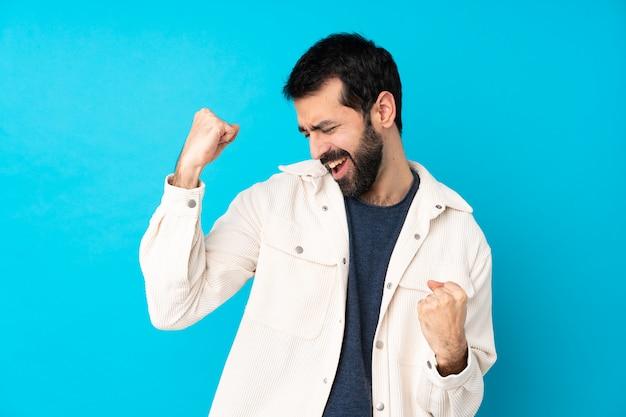 Junger hübscher mann mit weißer cordjacke über blau, der einen sieg feiert